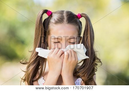Close-up of girl blowing her nose with handkerchief while sneezing in the park