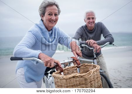 Portrait of senior couple standing with their bike on the beach