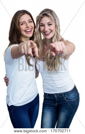 Portrait of two beautiful woman pointing towards camera on white background