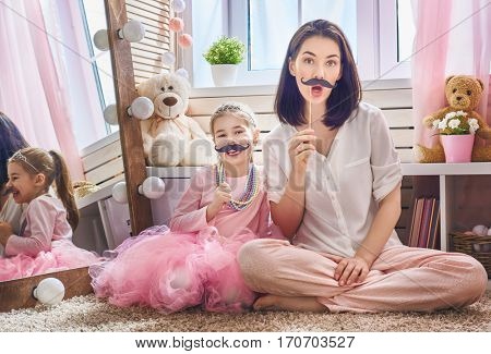 Funny family playing at home. Mother and her daughter girl with a paper accessories. Mom and child are holding paper mustache on sticks.