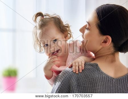 Happy loving family. Young mother are playing with her baby girl in the bedroom. Mom and child are having fun together.
