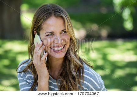 Smiling woman making a phone call in a park