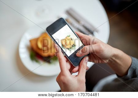 food, new nordic cuisine, technology, eating and people concept - woman with smartphone photographing breaded fish fillet with tartar sauce and oven-baked beetroot tomato salad at restaurant