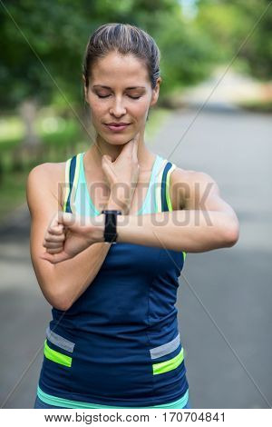 Sportswoman checking her heart rate watch in park