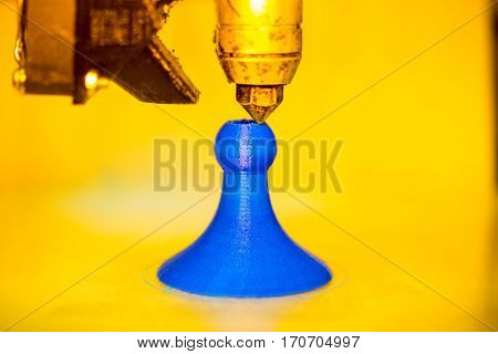 Modern 3D printer printing figure close-up macro.Automatic three dimensional 3d printer performs plastic yellow and blue colors modeling in laboratory. 3d-printing processing with white background