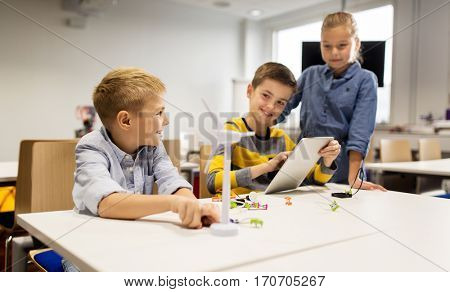 education, science, technology, children and people concept - group of smiling kids or students with tablet pc computer programming electric windmill toy at robotics school lesson