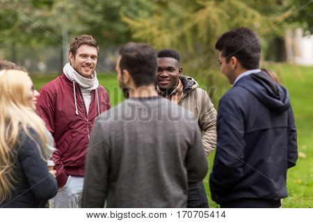 people, friendship, communication and international concept - group of happy friends outdoors