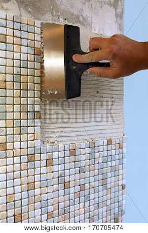 Repair in the apartment: installing the mosaic tile on the wall. A worker covers the wall with adhesive using a notched trowel.