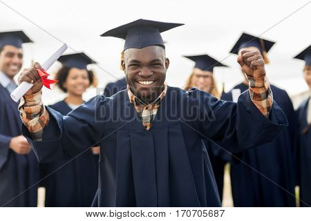 education, gesture and people concept - group of happy international students in mortar boards and bachelor gowns with diplomas celebrating successful graduation