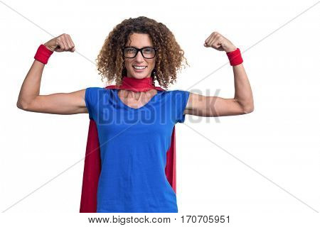 Portrait of smiling woman in superhero costume while flexing muscles on white background