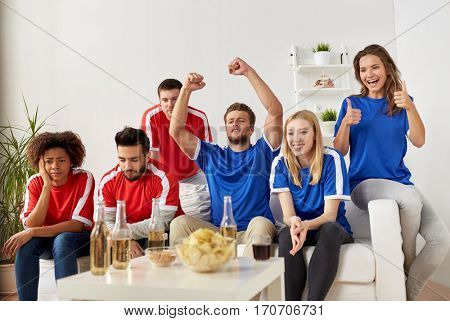people, leisure, rivalry and sport concept - happy and sad friends or football fans drinking beer and watching soccer game or match at home