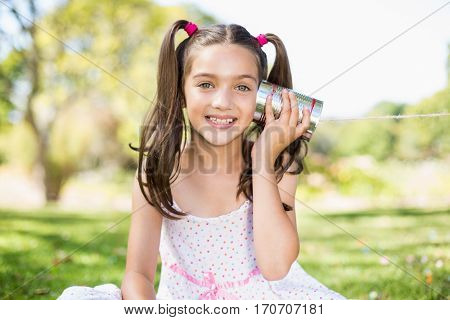 Portrait of young girl listening through tin can phone in park