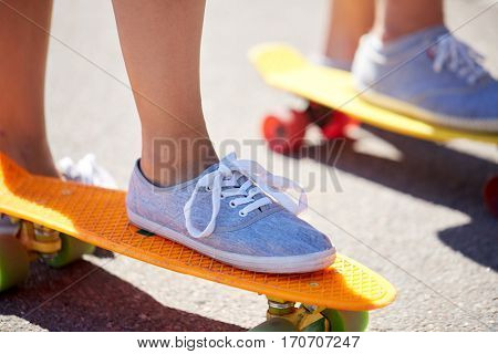 summer, extreme sport and people concept - close up of feet in shoes riding short modern cruiser skateboards on city street