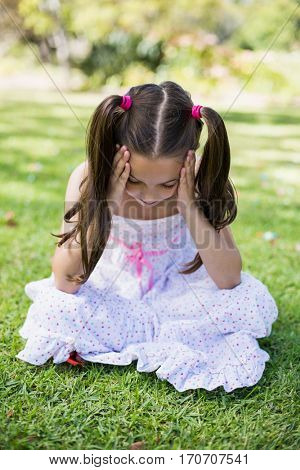 Upset girl sitting with hand on forehead in park