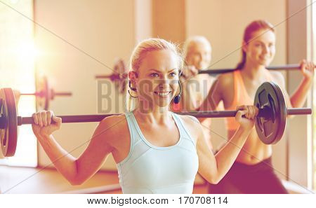 fitness, sport, training and lifestyle concept - group of happy women with barbells exercising in gym