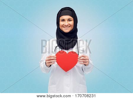 medicine, healthcare, charity and people concept - smiling muslim female doctor wearing hijab and white coat with red heart and stethoscope over blue background