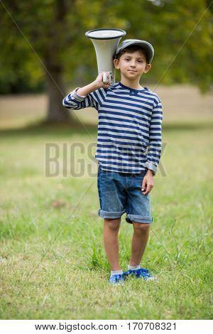Portrait of smiling boy holding megaphone in park