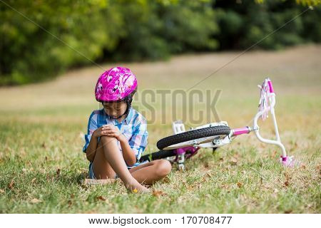 Young girl getting injured after fallen from bicycle in park