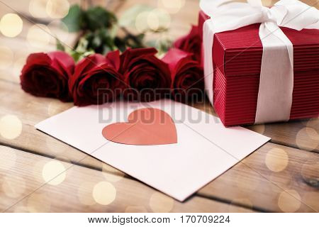 love, romance, valentines day and holidays concept - close up of gift box, red roses and greeting card with heart on wood (vintage effect)