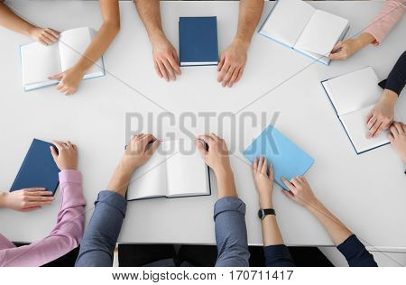 People sitting at table in book club