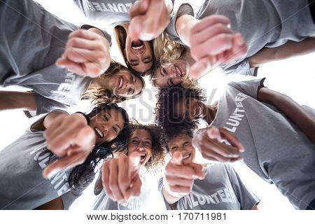 Happy volunteers pointing downwards against the sky