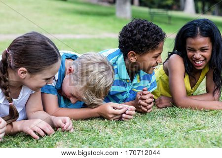 Happy children lying on grass in park