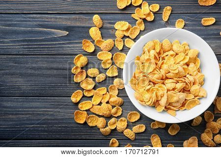 Bowl with cornflakes on grey wooden background