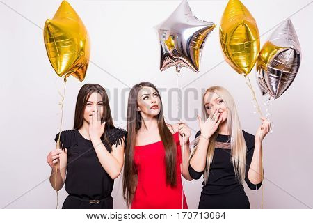 Three Lovely Young Women Standing And Holding Star Shaped Balloons Over White