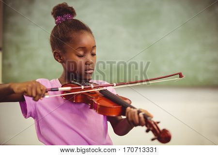 Schoolgirl playing violin in classroom at school