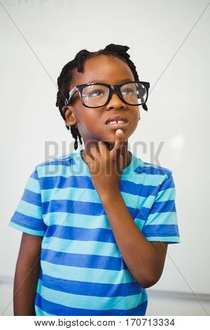 Thoughtful schoolboy standing with hand on chin in classroom at school