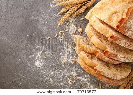 Sliced bread with wheat spikes and flour on grey table closeup
