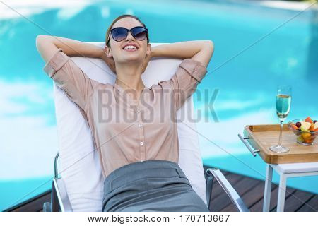 Business woman relaxing on sun lounger near pool