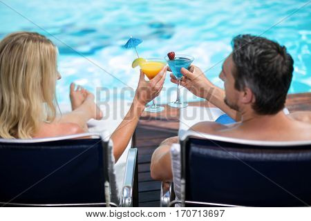 Rear view of couple toasting martini glass while relaxing on sun lounger near pool