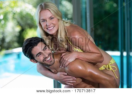 Man giving a piggy back to woman near the pool