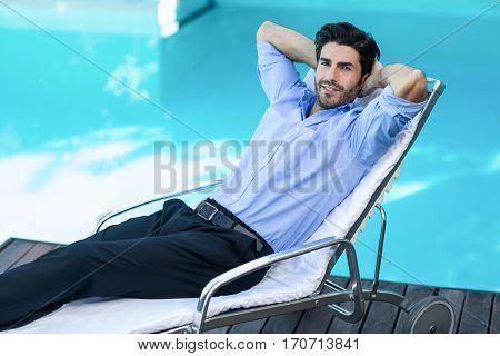 Portrait of smart man relaxing on sunlounger near pool
