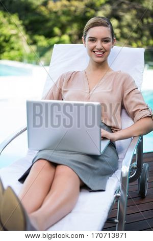 Portrait of businesswoman relaxing on sunlounger and using laptop near pool
