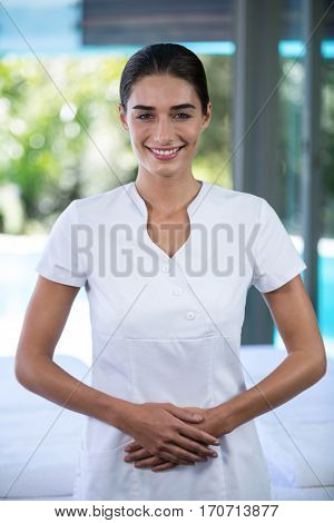 Portrait of confident female masseur standing in spa