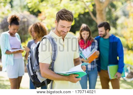 College boy reading notes with friends in background at campus