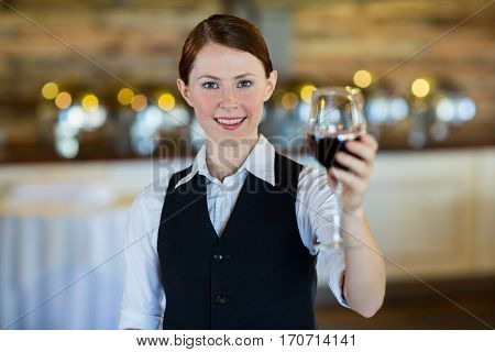 Portrait of waitress holding up a wine glass in restaurant