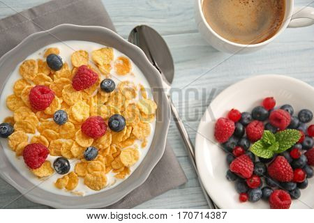 Tasty cornflakes with raspberries and blueberries on gray wooden background