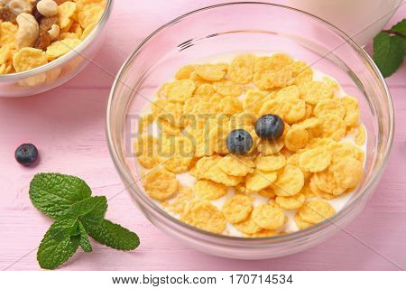 Tasty cornflakes with blueberries on pink background