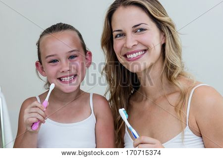 Portrait of happy daughter and mother holding a toothbrush in the bathroom at home