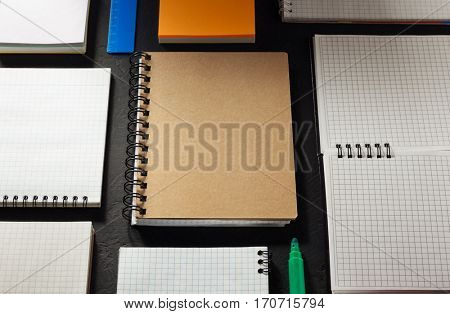 school supplies and notebook on black background