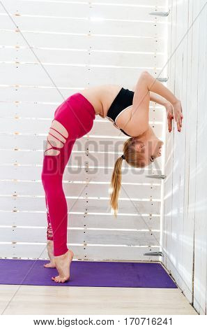 Woman practicing yoga. Yogi against the light from the window. Girl doing a handstand.