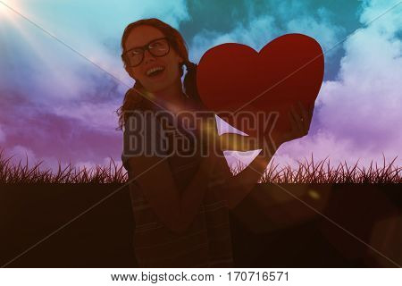 Geeky hipster woman holding heart card against sky and field