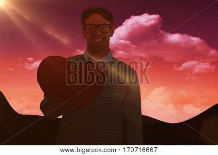 Geeky hipster holding heart card against sky and mountains