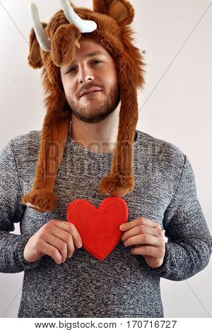 Funny man wearing mammoth cap holding a red heart