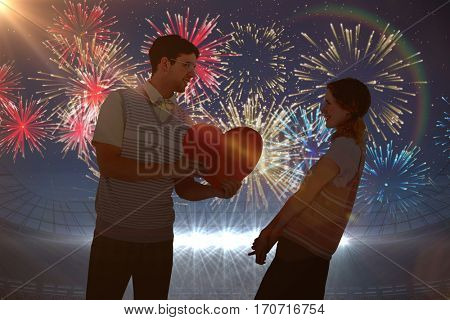 Geeky hipster giving heart card to his girlfriend against fireworks exploding over football stadium