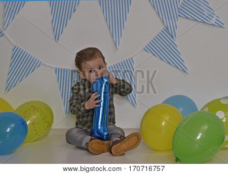 One year birthday baby party and balloons. Inflating number one balloon.