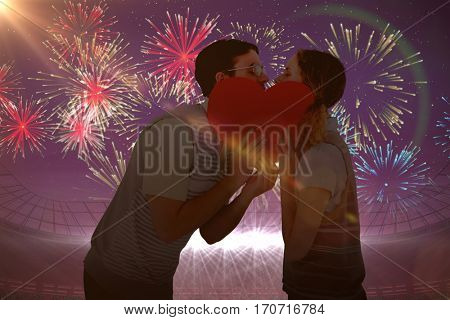 Geeky hipster couple kissing behind heart card against fireworks exploding over football stadium